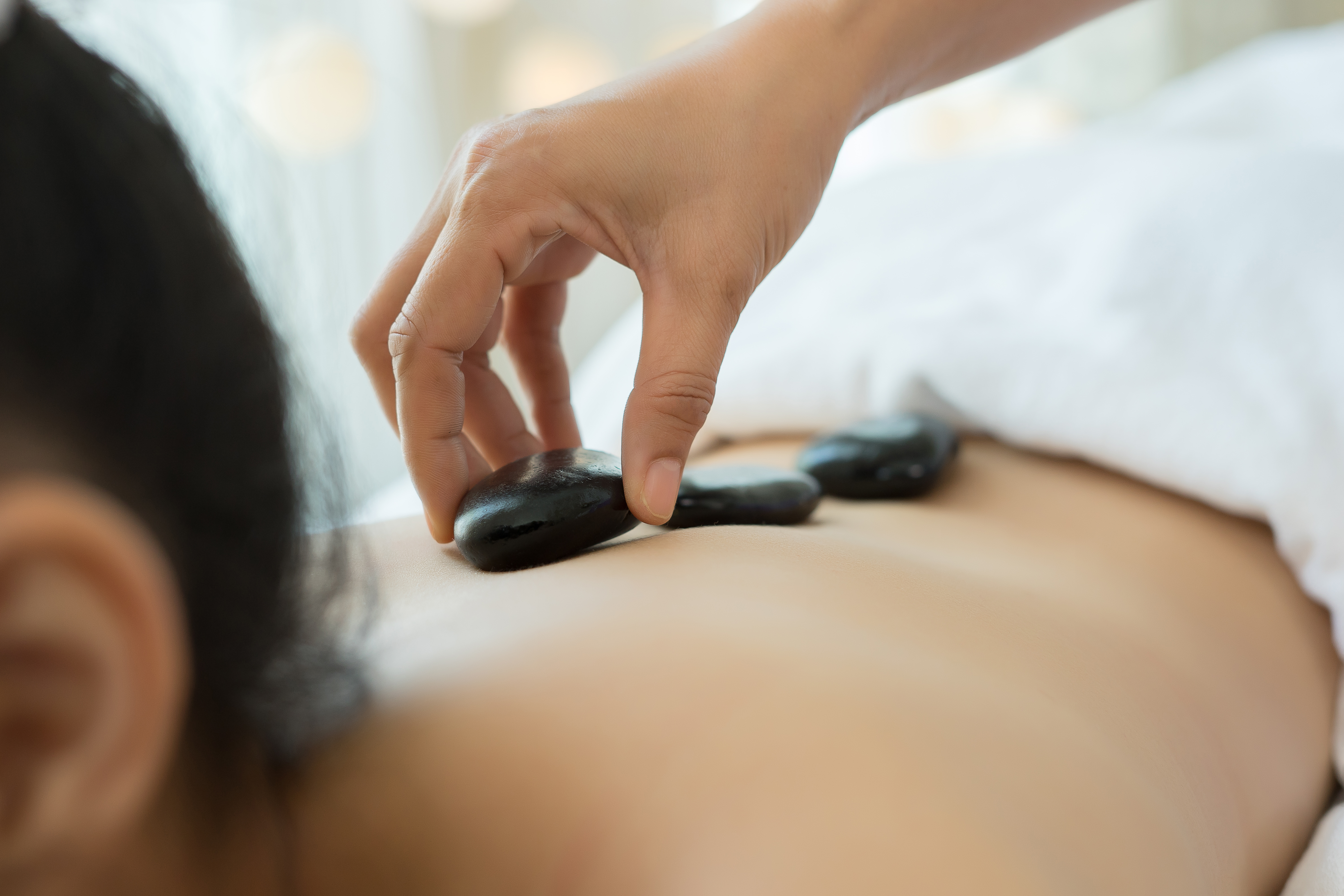 Young beautiful woman getting hot stone spa treatment.